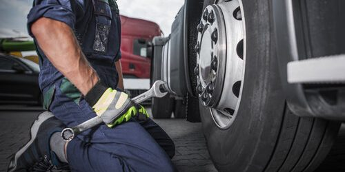 Caucasian Truck Mechanic with Large Wrench in His Hand Perform Scheduled Vehicle Maintenance. Looking on the Semi Truck Wheel and Tire.